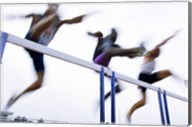Low angle view of three men jumping over a hurdle Fine-Art Print