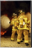 Rear view of three firefighters extinguishing a fire Fine-Art Print