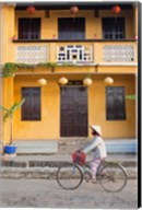 Person riding a bicycle in front of a cafe, Hoi An, Vietnam Fine-Art Print