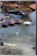 A Blackhawk helicopter drops sandbags into an area where the levee broke due to Hurricane Katrina Fine-Art Print