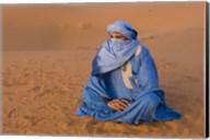 Veiled Tuareg man sitting cross-legged on the sand, Erg Chebbi, Morocco Fine-Art Print
