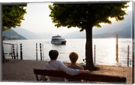 Couple sitting on bench and watching ferry approaching dock along the Lake Como, Bellagio, Province of Como, Lombardy, Italy Fine-Art Print
