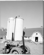 USA, Farmer Working on Tractor, Agricultural Buildings in the Background Fine-Art Print