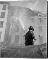 Firefighter pouring water on burning building, low angle view Fine-Art Print