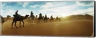 Tourists riding camels through the Sahara Desert landscape led by a Berber man, Morocco Fine-Art Print