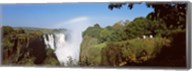 Tourists at a viewing point looking at the rainbow formed over Victoria Falls, Zimbabwe Fine-Art Print