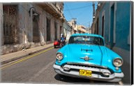 Cuba, Camaquey, Oldsmobile car and buildings Fine-Art Print