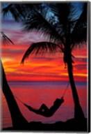 Woman in hammock, and palm trees at sunset, Fiji Fine-Art Print